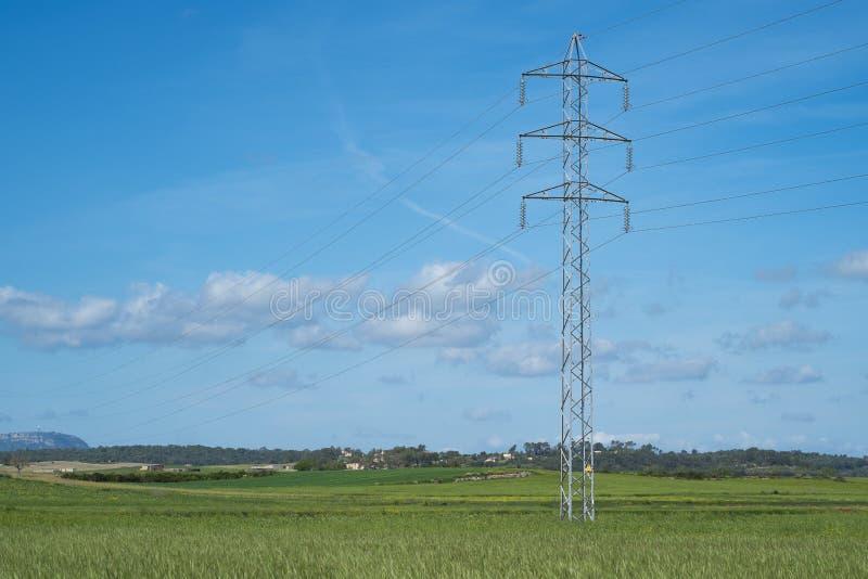 La tour et le câble à haute tension rayent dans la campagne sous un ciel bleu photo libre de droits