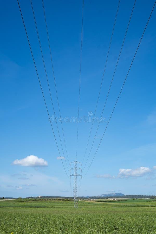 La tour et le câble à haute tension rayent dans la campagne sous un ciel bleu image libre de droits
