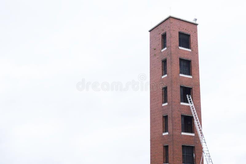La tour pour la formation de secours des sapeurs-pompiers pratiquent et échelle contre l'installation de brique rouge et le ciel  images libres de droits