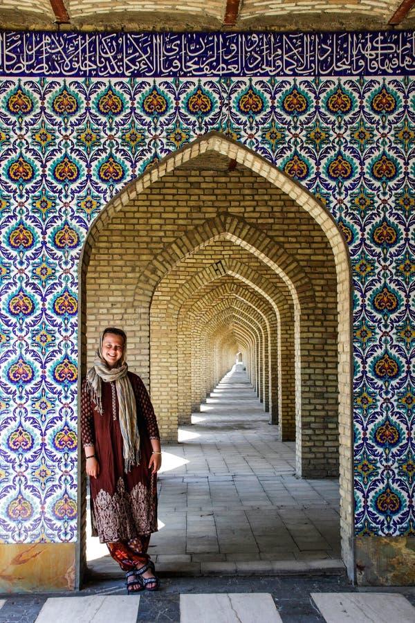 La touriste blanche de fille avec une tête a couvert des supports près de la belle porte décorée dans le style persan photographie stock