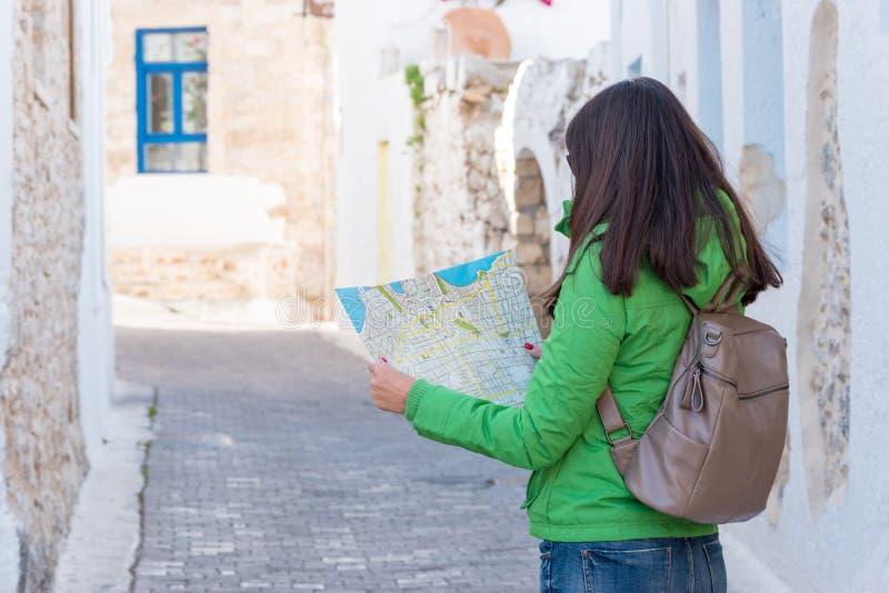 La touriste de femme regarde la carte sur la rue photo stock