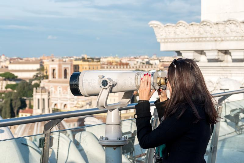 La touriste de femme regarde par des jumelles sur la ville image libre de droits