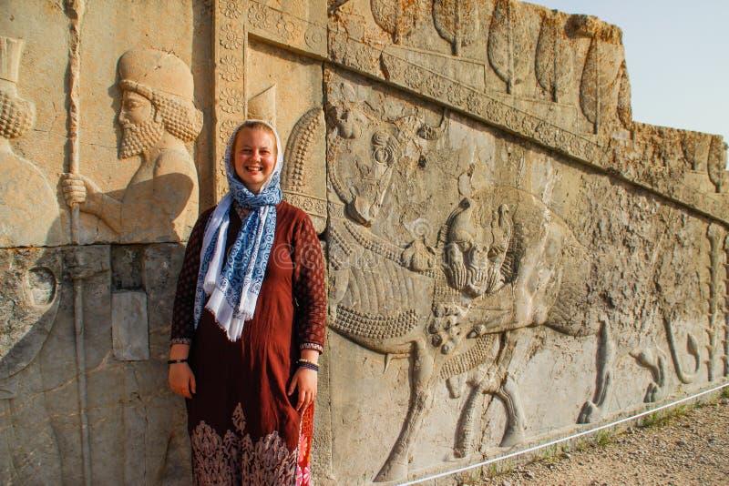 La touriste de jeune femme avec une tête couverte se tient sur le fond des bas-reliefs célèbres de la capitale de jour de Persia  image stock