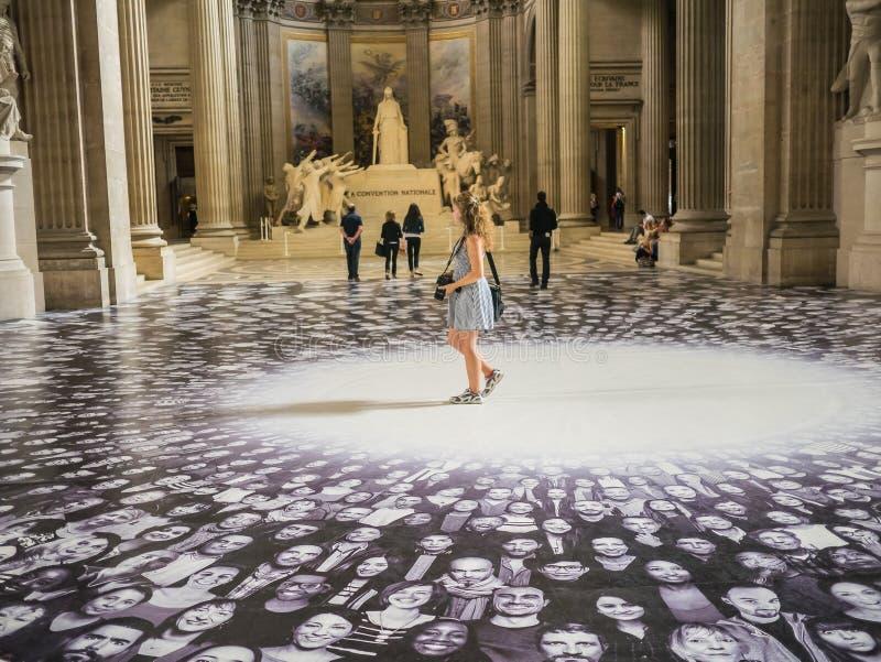 La touriste de jeunes femmes marche par le JR affichage dans le Panthéon de Paris image stock