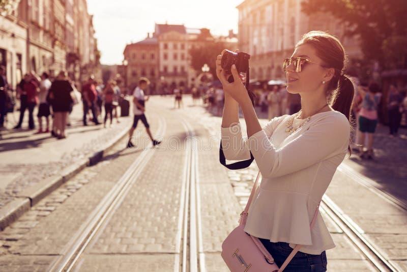 La touriste heureuse de jeune femme prend des picures dans la vieille ville Course d'été Vacances et concept de vacances photos libres de droits
