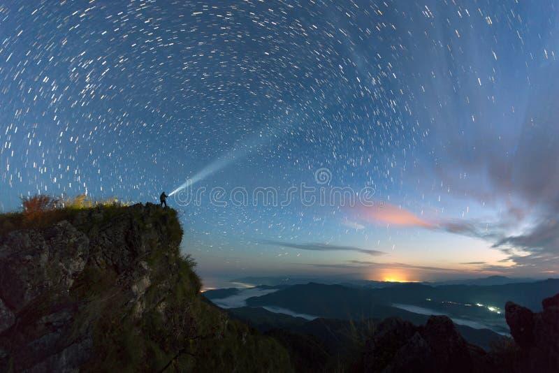 La traînée d'étoile au-dessus de la montagne avec l'homme allument le ciel avant image stock