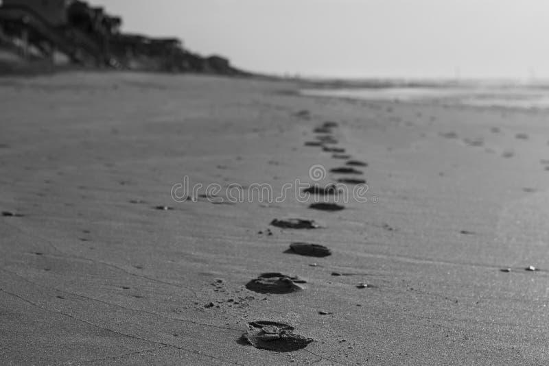 La traînée des empreintes de pas sur la plage se fanent dans la vue photographie stock libre de droits
