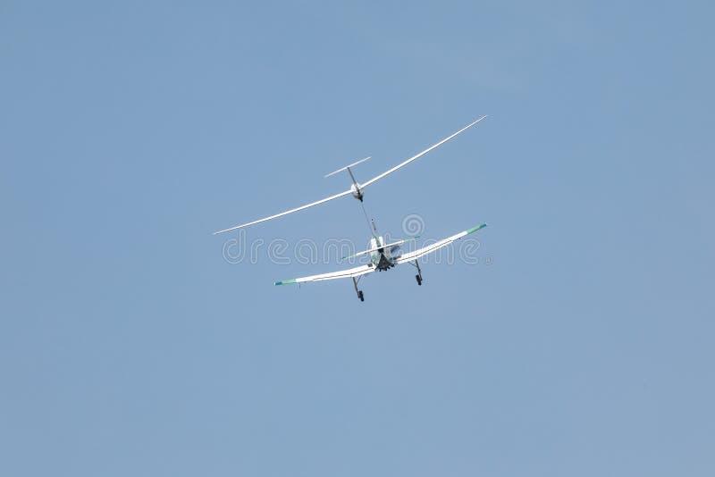 La tracción plana de un planeador, un pequeño avión de los deportes tira de un planeador en la nube foto de archivo