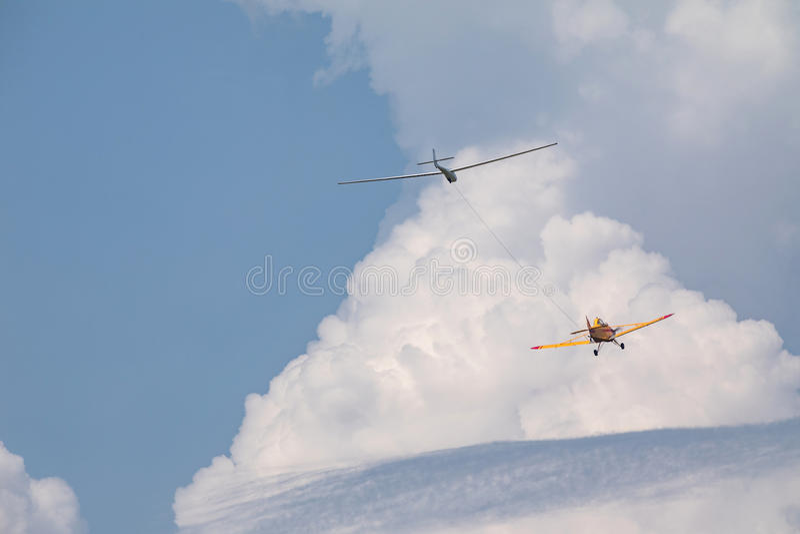 La tracción plana de un planeador, un pequeño avión de los deportes tira de un planeador en la nube fotos de archivo libres de regalías