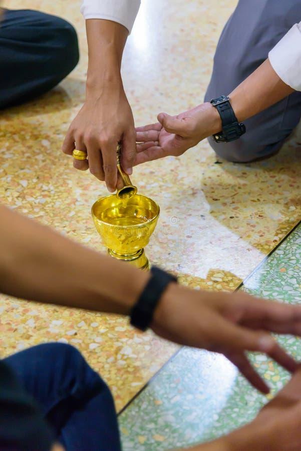 La tradición tailandesa, agua de colada es un acto de la rogación foto de archivo
