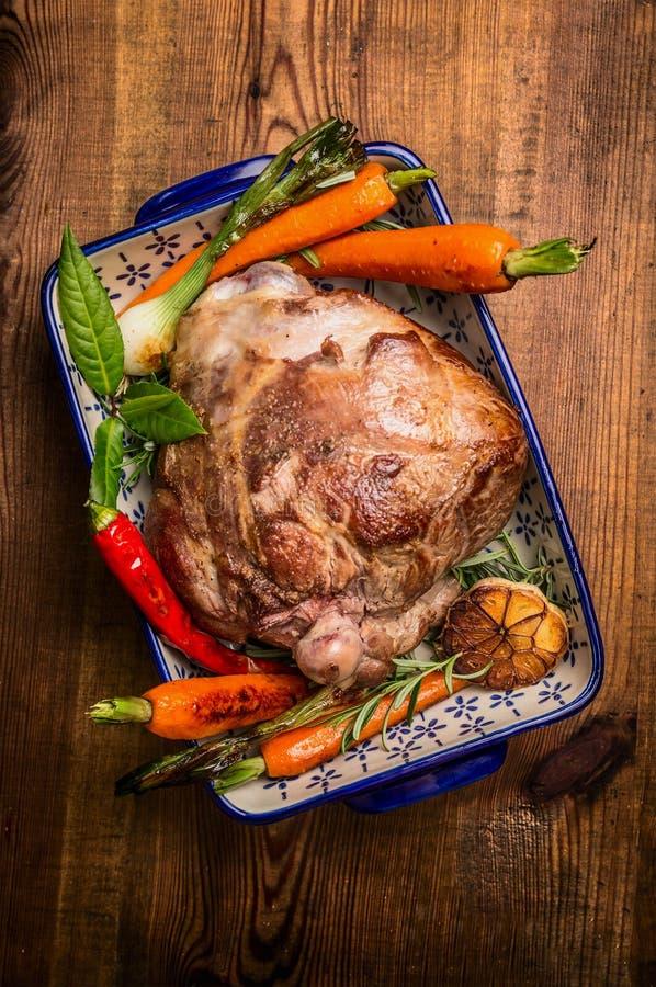 La tradition a rôti la jambe d'agneau avec la carotte et les herbes fraîches dans la cuvette rustique sur le fond en bois photographie stock