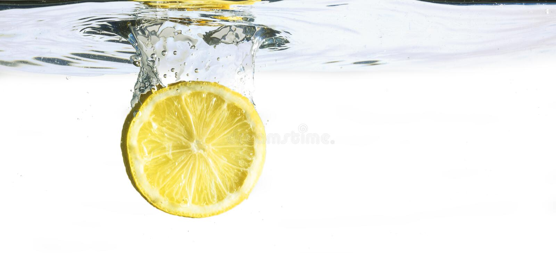 La tranche de citron tombe dans l'eau, d'isolement sur un backg blanc image stock