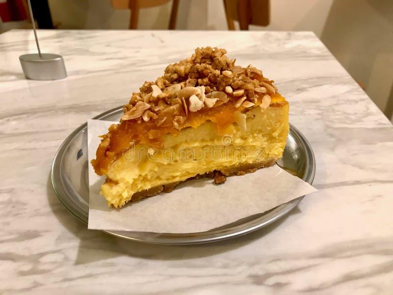 La tranche de gâteau au fromage de potiron avec les écrous et les amandes croustillants a servi au café avec le magasin de plat a images libres de droits