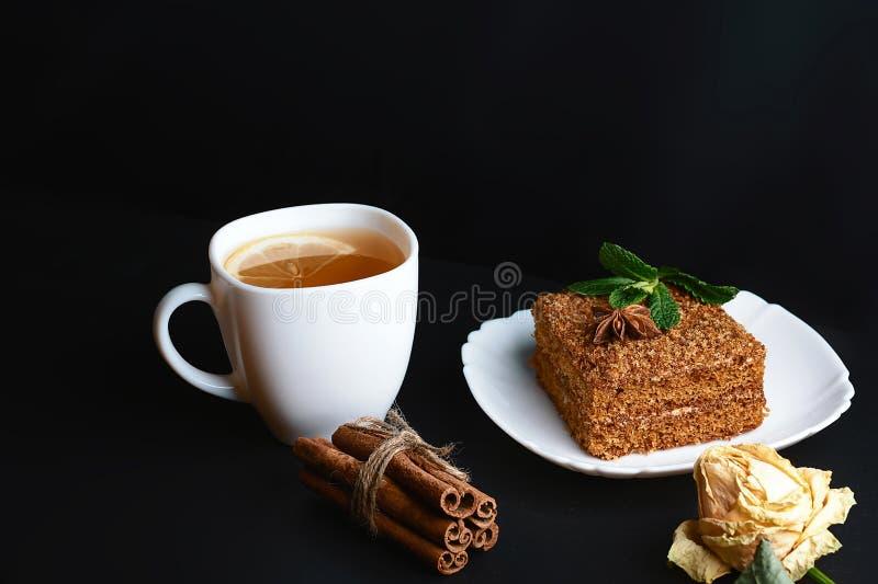 La tranche de gâteau de miel posé Medovik décorée de la menthe du plat blanc, les bâtons de la cannelle, une tasse de thé avec le photo stock