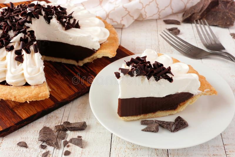 La tranche de tarte crème de chocolat, se ferment vers le haut de la scène de table contre le bois blanc image stock