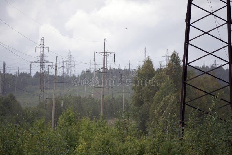 La transmission électrique à haute tension domine des pylônes et des lignes électriques de l'électricité sur le champ vert image stock
