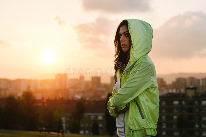 La travesía urbana del atleta de sexo femenino arma en puesta del sol y fondo de la ciudad imagen de archivo libre de regalías