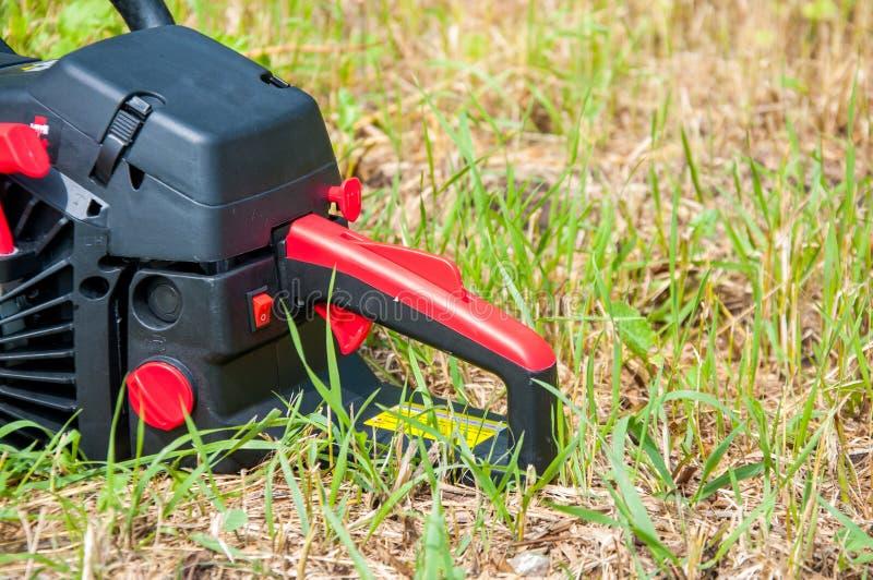 La tronçonneuse noire se trouve sur l'herbe verte photographie stock
