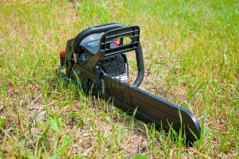 La tronçonneuse noire se trouve sur l'herbe verte photos stock