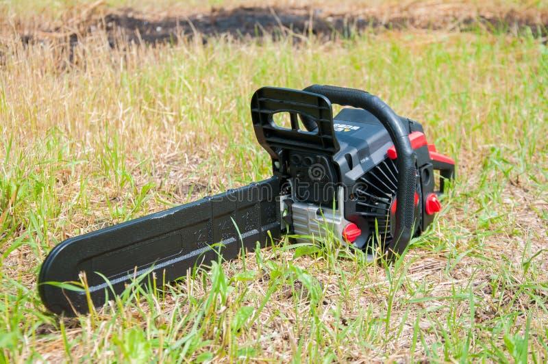 La tronçonneuse noire se trouve sur l'herbe verte images libres de droits