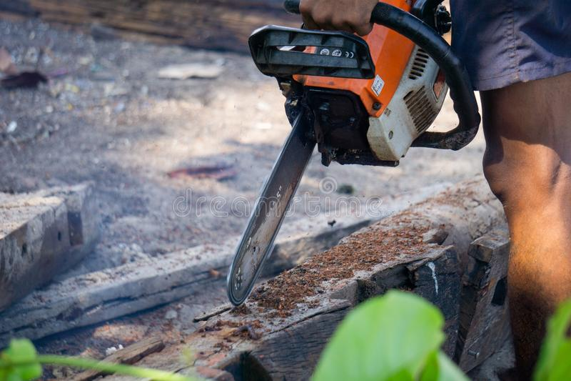 La tronçonneuse portative de moteur à essence d'utilisations d'homme a coupé le bois de construction en morceaux image libre de droits