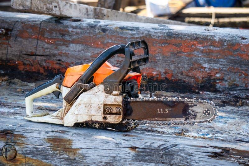 La tronçonneuse portative de moteur à essence orange a mis dessus la vieille planche en bois photographie stock libre de droits