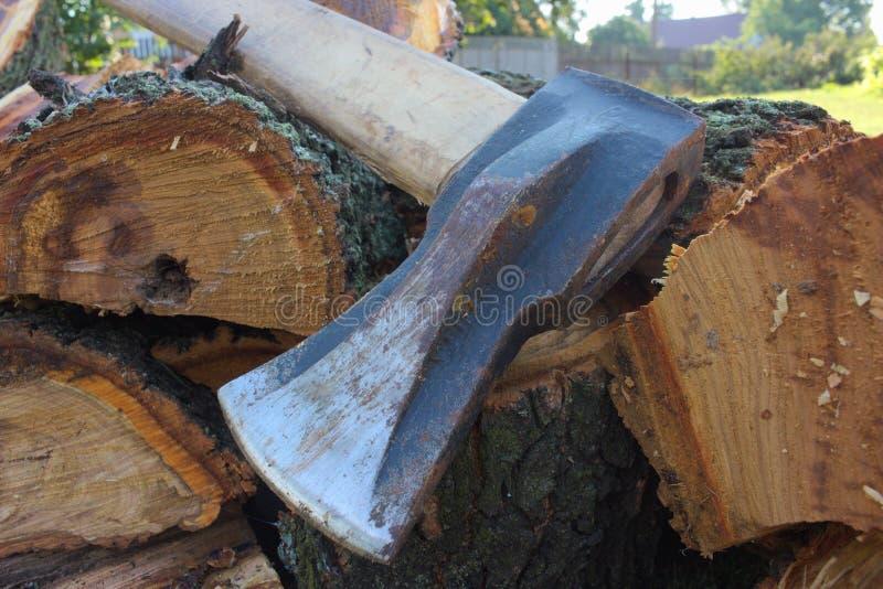 La tronçonneuse se trouve sur le bois de chauffage photos stock