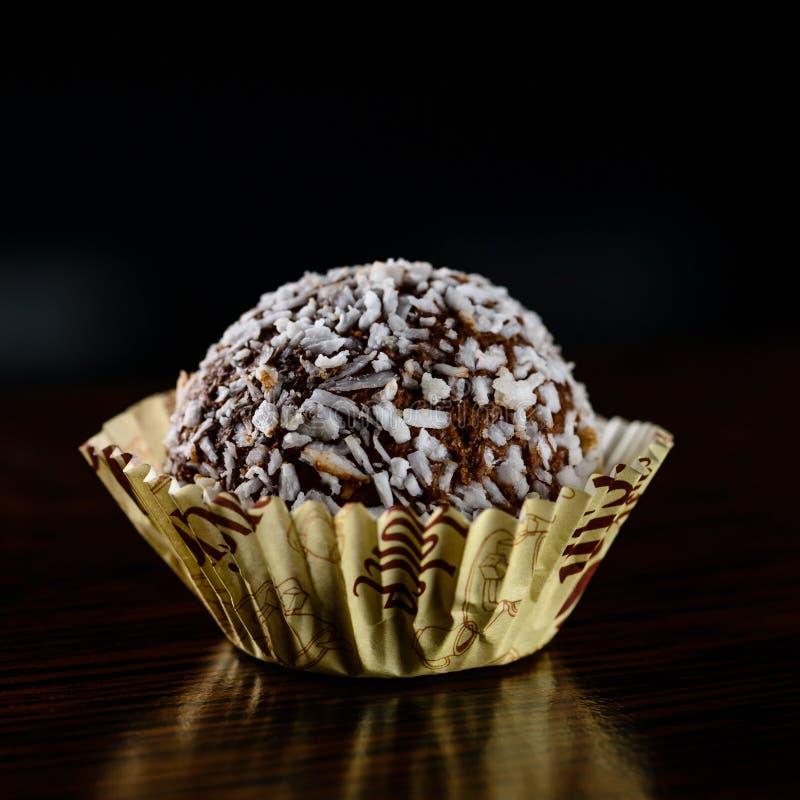 La trufa del coco del chocolate con el coco forma escamas en fondo oscuro imagen de archivo