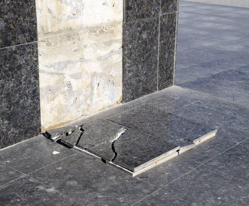 La tuile de marbre ruinée qui est tombée de la base du monument image stock