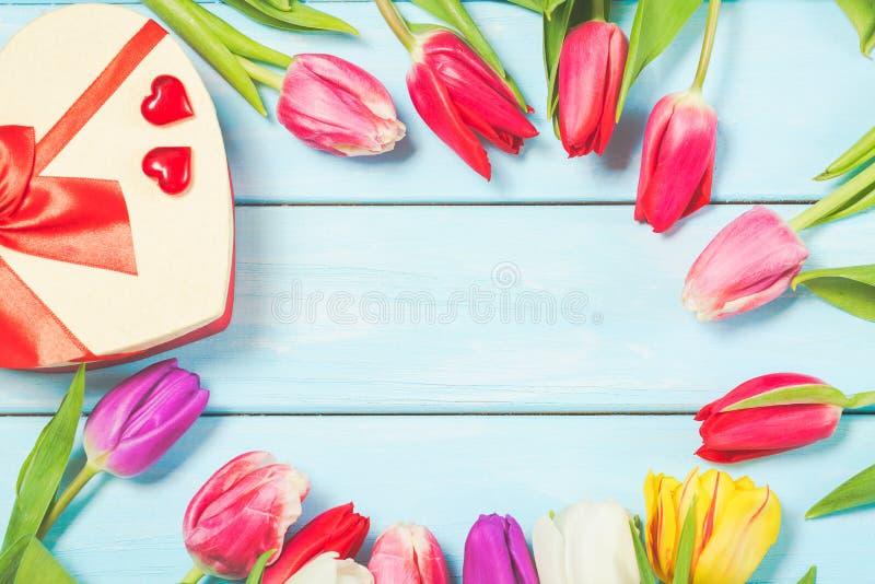 La tulipe colorée de ressort fleurit avec le giftbox et les coeurs décoratifs sur le fond en bois bleu-clair comme carte de voeux images stock