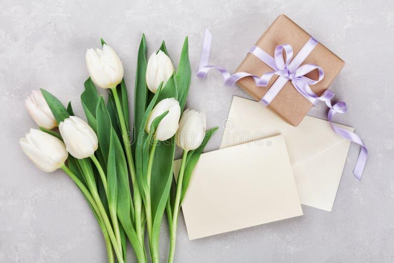 La tulipe de ressort fleurit, boîte-cadeau et la carte de papier sur la table en pierre grise de ci-dessus dans l'appartement éte image stock