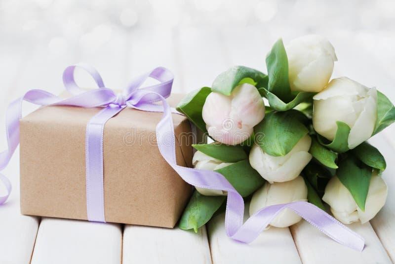 La tulipe de ressort fleurit et boîte-cadeau avec le ruban d'arc sur la table blanche Carte de voeux pour le jour d'anniversaire, image stock