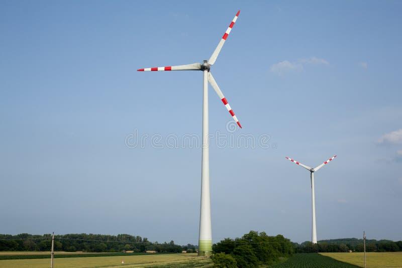 La turbina de viento es la energía limpia para guardar limpia la tierra central eléctrica de energía eólica en prado verde contra imagen de archivo libre de regalías