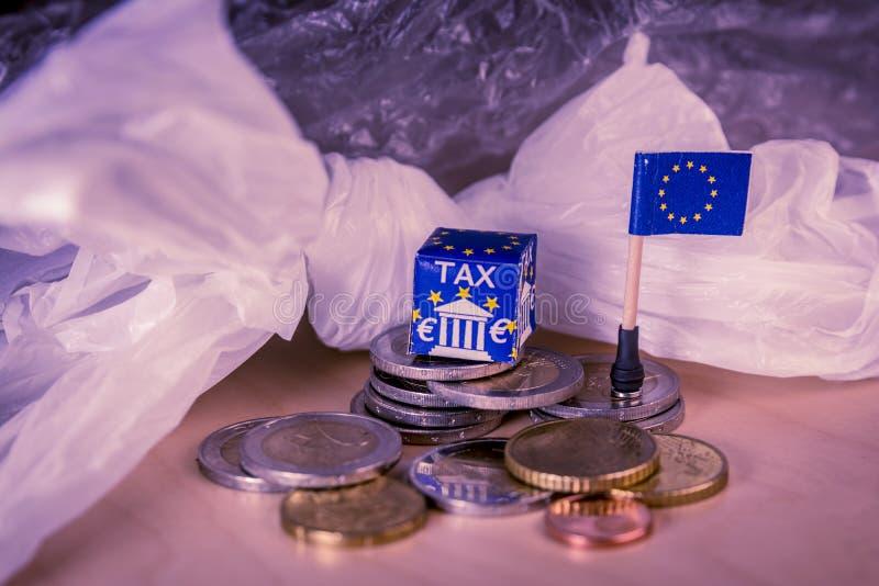 La UE traza con monedas euro y una bolsa de plástico que simboliza la regulación de impuesto plástica europea fotografía de archivo