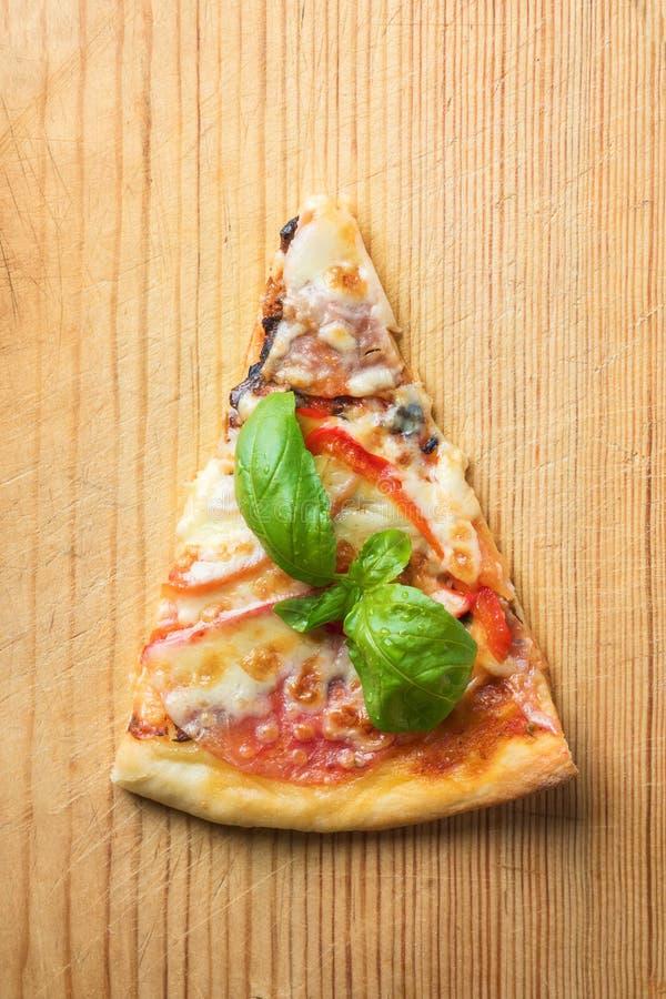 La una pieza de la pizza italiana con los tomates prolifera rápidamente tocino y el queso y la albahaca se va en tabla de cortar  imagen de archivo