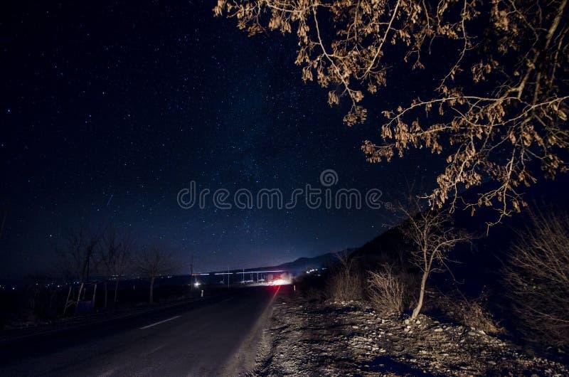 La vía láctea sobre un camino y un árbol cercanos para arriba con el coche se enciende en brenches Camino de la noche con las est imagen de archivo