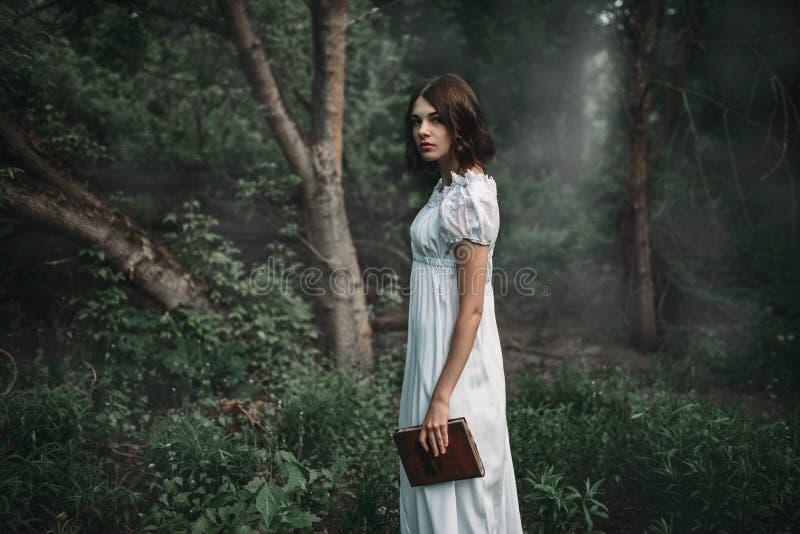 La víctima femenina en el vestido blanco sostiene el libro disponible fotografía de archivo libre de regalías