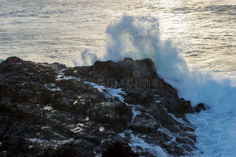 La vague forte rencontre des roches de lave sur la côte photo libre de droits