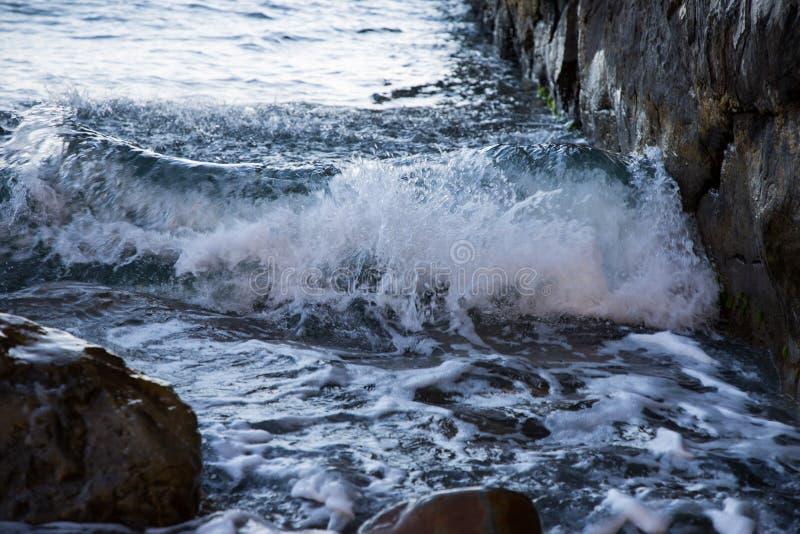 La vague roule sur les roches vague déferlante noire Ukraine de mer de la Crimée de côte Mouvement gelé photos libres de droits