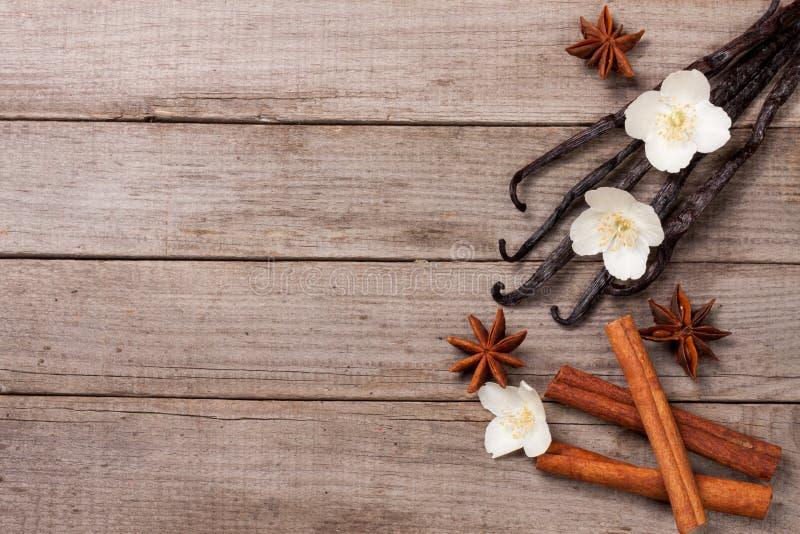 La vainilla se pega con canela y la flor en un viejo fondo de madera con el espacio de la copia para su texto Visión superior imagenes de archivo