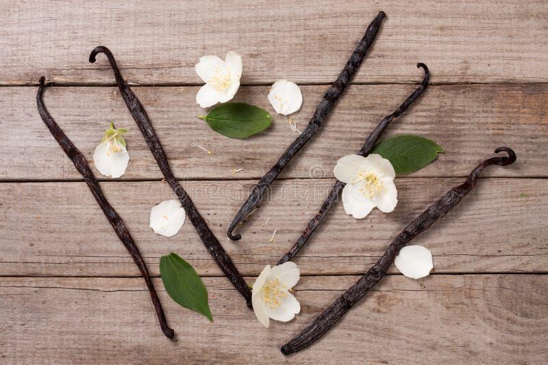 La vainilla se pega con la flor y la hoja en un viejo fondo de madera imagen de archivo libre de regalías