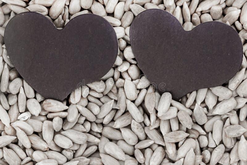 La valentine de saint de jour d'amour de symbole sur des graines de tournesol de fond a épluché la base rustique de fond de cultu image stock