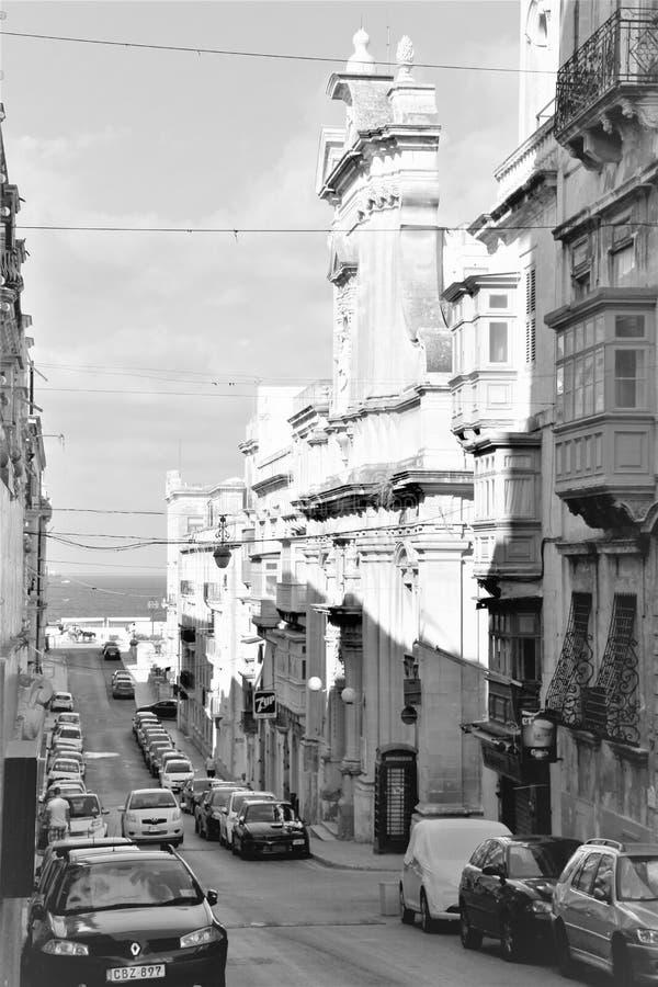 La Valeta, Malta, agosto de 2015 Vista blanco y negro de la calle vieja y de los coches modernos en ella imagenes de archivo
