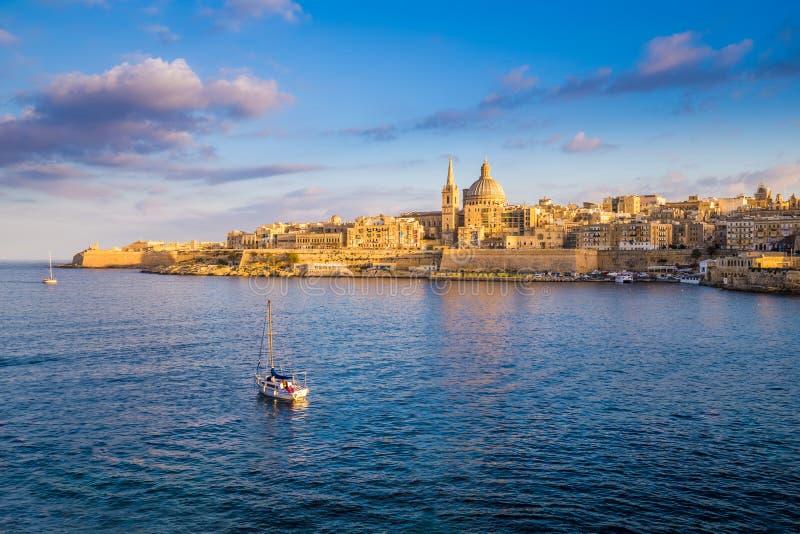 La Valeta, Malta - barco de vela en las paredes de La Valeta con la catedral del ` s de StPaul fotografía de archivo