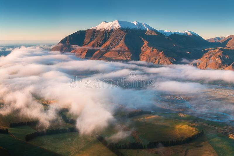 La valle ? sommersa in foschia in un ambiente della montagna Sopra annebbia, solo gli alti picchi delle montagne fotografia stock libera da diritti