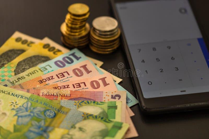 La valuta rumena LEI sullo sfondo nero con calcolatrice mobile Denaro, tasse, concetto di notizie immagine stock libera da diritti