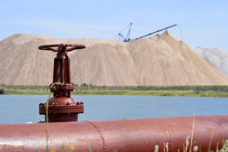 La valvola dalla conduttura contro lo sfondo di una miniera di sale e di un lago artificiale fotografia stock