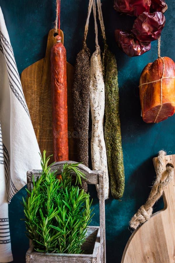 La variedad de español curó los productos de carne, charcuterie, romero fresco, tabla de cortar de madera, colgando en los gancho imagen de archivo libre de regalías