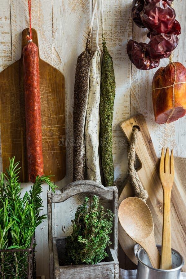 La varietà di Spagnolo ha curato i prodotti a base di carne, charcuterie, rosmarino fresco, tagliere di legno, utensili della cuc immagine stock