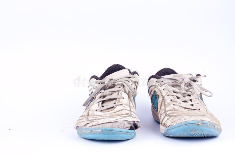 La vecchia annata ha danneggiato le scarpe futsal di sport su fondo bianco isolato immagine stock